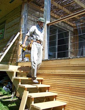 A photo of Michael walking down some wooden steps with a power drill in hand.