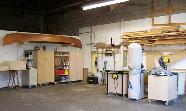 A workshop with pieces of wood on shelves and power tools all around.