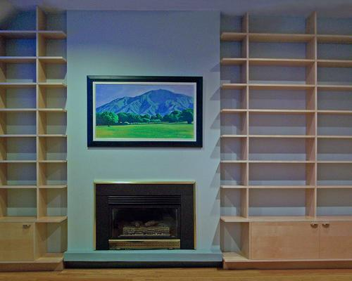 A head on view of a fireplace with wood bookshelves built into the walls on either side, and a painting above the fireplace.