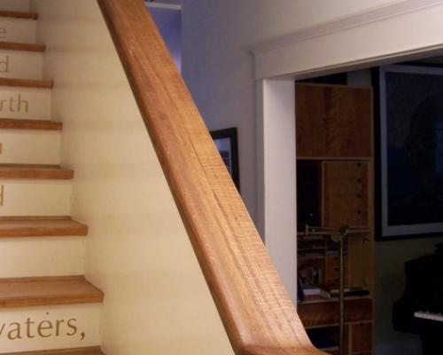 A photo looking up a set of stairs with a wide, wood handrail.