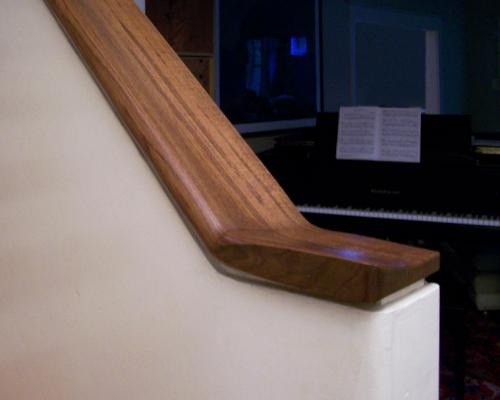 A close up of a wide, wood handrail.