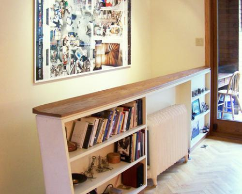 A 45 degree view of the shelves built into the guard rail for stairs, with books on the shelves on either side of a radiator.