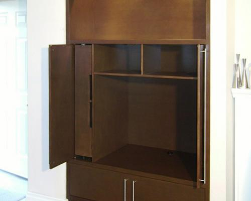 The entertainment unit with the top, large doors opened. it is empty with one large compartment for the TV, and several smaller compartments.