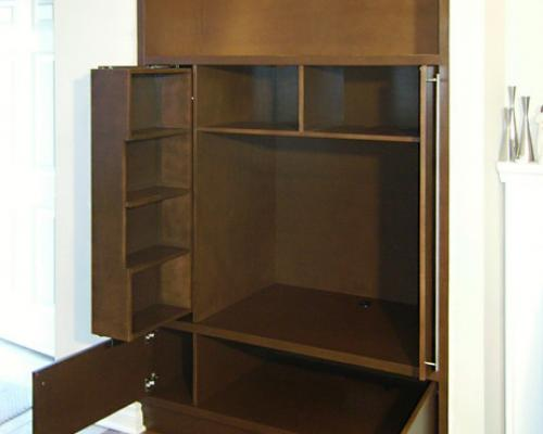 The entertainment unit, opened, with the CD/DVD shelf sliding out from the left of the TV compartment.