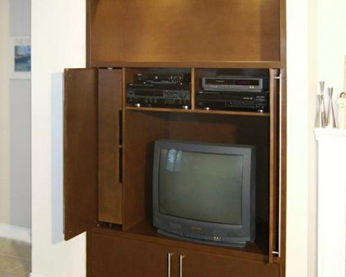 The entertainment unit with a TV and various home theatre equipment in the compartments. The TV is an older, tube set.