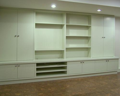 A series of shelves and compartments covering an entire wall. They are white, and empty.