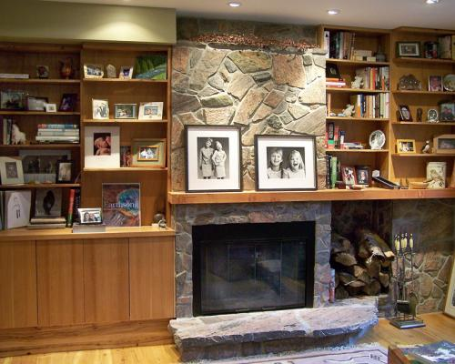 A photo of bookshelves, storage and mantelpiece around a stone fireplace.