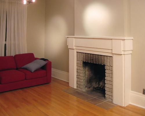 A fireplace with a white, wood mantelpiece.