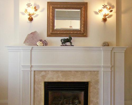 A fireplace with a white, wood mantelpiece surrounding it.