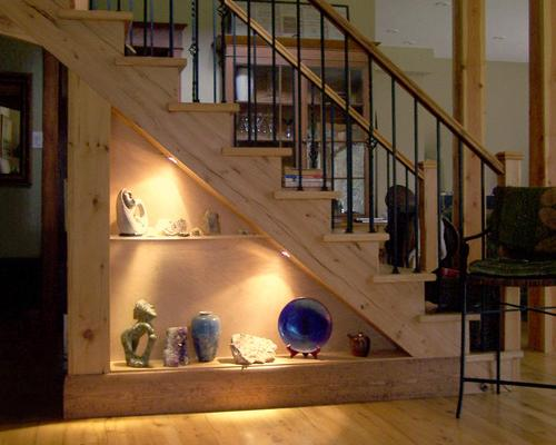 A display unit housing various sculptures, cut out of a triangle under some stairs.