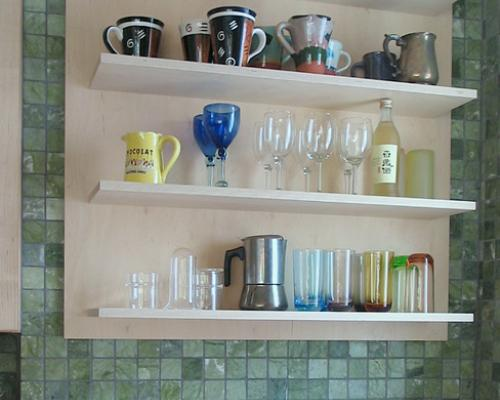 A close up of a shelf with various cups and glasses on it.