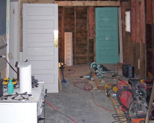 A view into the long and narrow kitchen, during construction. Exposed wall and roof structures are visible.
