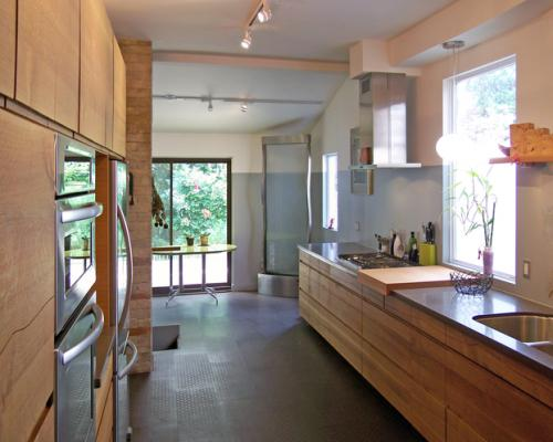 A photo of a long, somewhat narrow kitchen, with wood cabinets on both sides and underneath the counter.