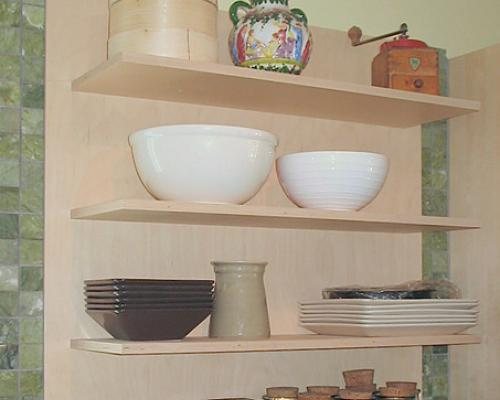 A close up of a shelf with various bowls on it.
