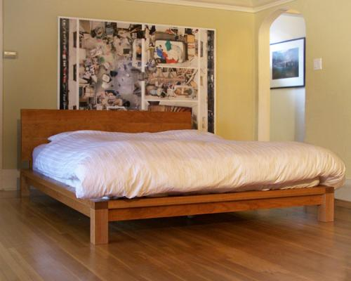 A simple, queen size bed made of wood, with a large, wood headboard.
