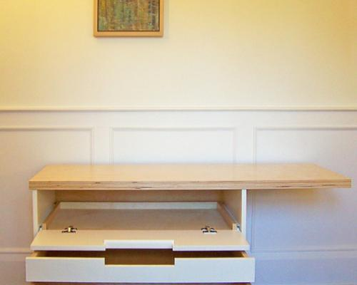 A wood cabinet/desk, with the cabinet under the desk open to reveal several drawers/compartments.