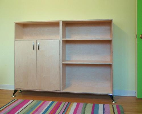 A combination cabinet and shelves, up to waist height, made of wood.