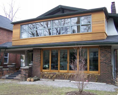 A house with tall windows on the ground floor with cedar frames, and a second floor with a row of windows with cedar on all sides.