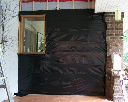 The house's porch, covered in plastic wrap, under construction, before the installation of the cedar panels.