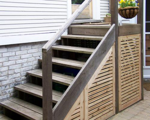 Stairs with slotted wood covering the area under the stairs.