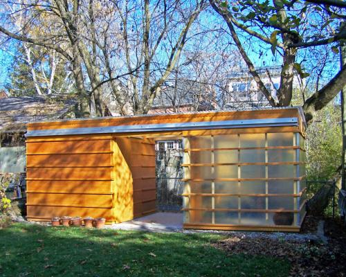 A cedar shed with a walkway between a solid section on one side and on the other side a section with a sliding door covered in frosted glass or plastic.