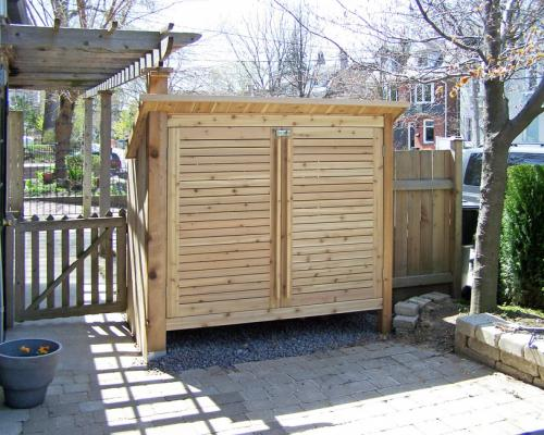 An armoire, built into a fence. It has slotted doors and a roof that slants backwards.