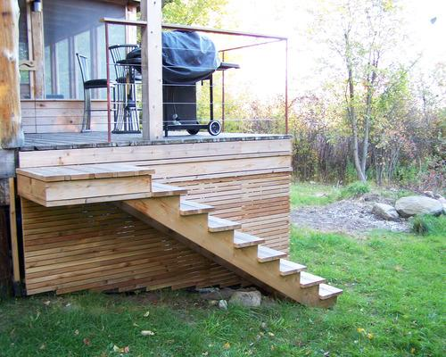 A photo of some cedar stairs along the side of the cottage, leading up to the porch. A barbecue is on the porch.