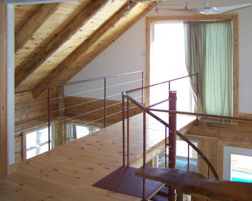 A photo of the bridge on the second floor of the cottage, leading to a front deck.