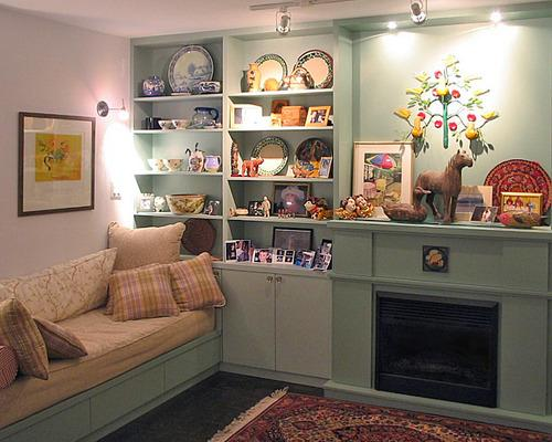 A photo of shelves built around a fireplace, with a day bed/sofa to the side.